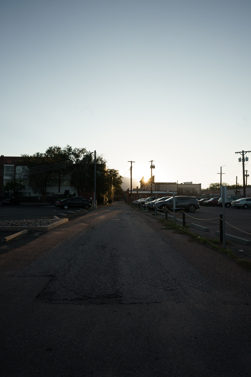 picture of an empty alley with the sun shining past the top of a building just before sunset
