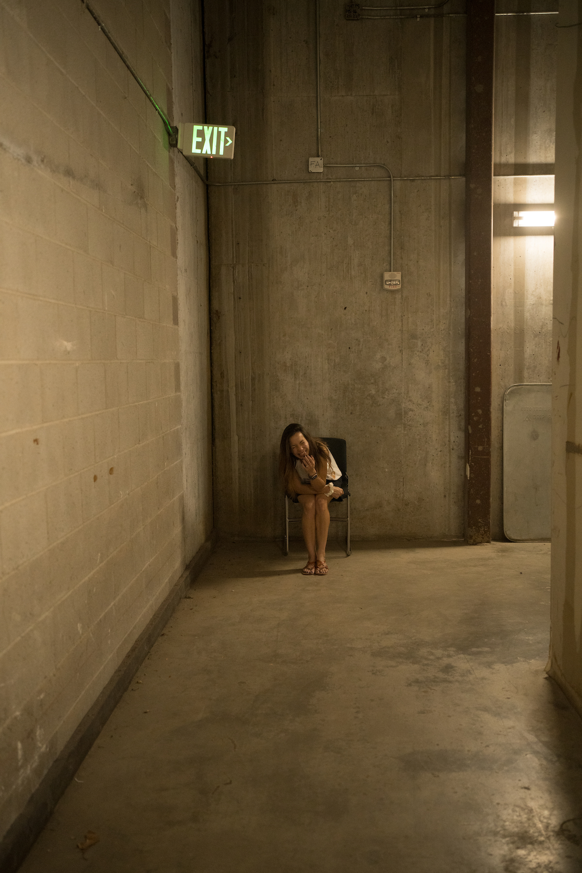 picture of Chris' wife laughing under a green 'EXIT' sign in a concrete-walled mall hallway